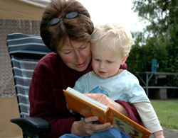 woman sitting in a lawn chair, reading to a young boy on her lap
