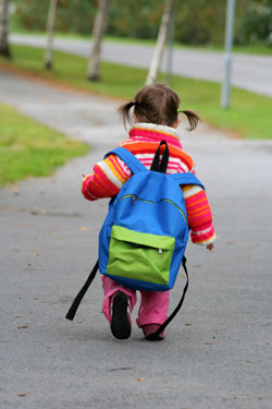 little girl walking away down a path with a backpack on