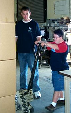 Young man with Down Syndrome learning how to lift a stack of boxes with a mechanical lift