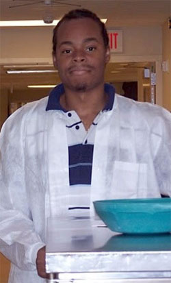 Young man in a lab coat standing in a hospital hallway