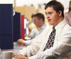 young man with Down Syndrome, working at a desk with a cup of coffee next to his keyboard